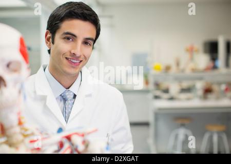 Retrato de sonriente científico con modelo anatómico n laboratorio