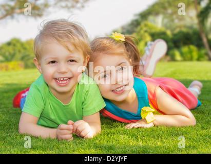 Imagen de hermano y hermana divertirse en el parque, dos niños alegres, por el que se establecen en el pasto verde, niña y niño jugando