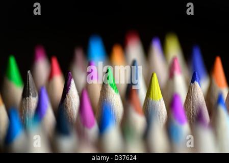 Cerrar fotografía de lápices de colores brillantes con un fondo negro.
