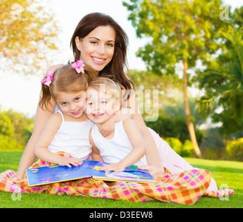 Imagen de familia feliz, joven madre de dos hermosos hijos lindo divertirse al aire libre en primavera