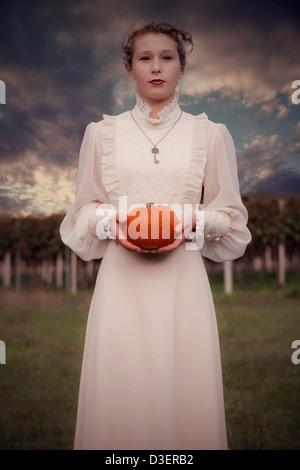 Una mujer en un vestido victoriano está celebrando una calabaza Foto de stock