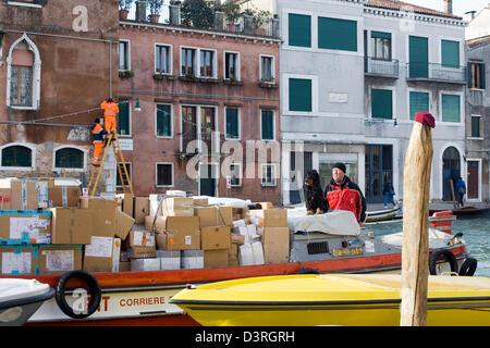 El hombre ad su perro transportar mercancías en un barco en la ciudad Venecia Italia