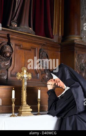 Capilla del siglo xvii de una iglesia medieval y un joven novicio en la oración Foto de stock