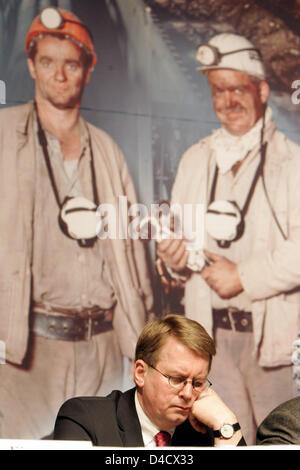 """El gerente general de 'RAG Deutsche Steinkohle' Mining Company, Bernd Toenjes retratado delante de una gran fotografía que muestra dos mineros por delante de la empresa la obra extraordinaria celebrada en Saarbrücken, Alemania, el 26 de febrero de 2008. Un terremoto relacionadas con la minería llegando a 4,0 en la escala de Richter """"sacudió la región del Sarre el 23 de febrero de 2008. Desde entonces, la labor recae en el Sarre, la única"""