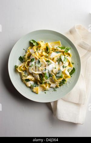 Un plato de pasta pappardelle con crema de requesón, baby de espinacas frescas, hierbas y pimienta negra. Foto de stock