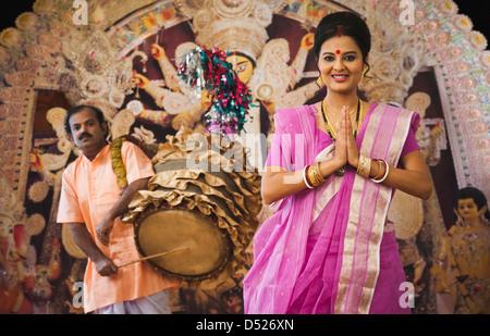Mujer bengalí de pie en una posición de oración y una reproducción Dhak Dhaki en Durga Puja Foto de stock
