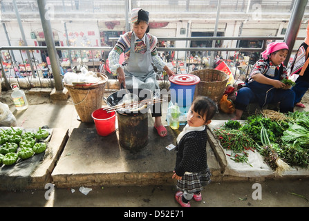Niño de espera para ser atendido en un puesto de comida en el mercado Yuanyang en la provincia de Yunnan, en China
