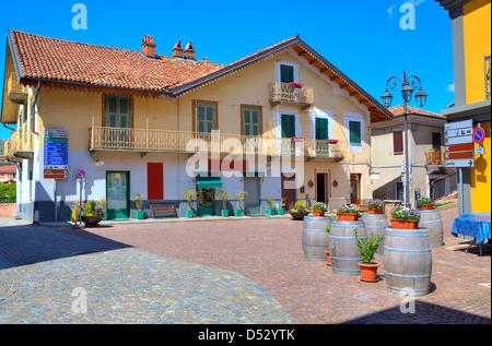 Vista de la pequeña plaza adoquinada en el centro de un típico pueblo italiano entre coloridas casas en Barolo, Italia.