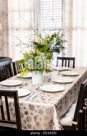 Mesa de comedor decorado para la Navidad con ocho ajustes de lugar y evergreen central
