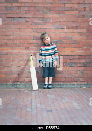 Chico con el bate de críquet contra la pared de ladrillo