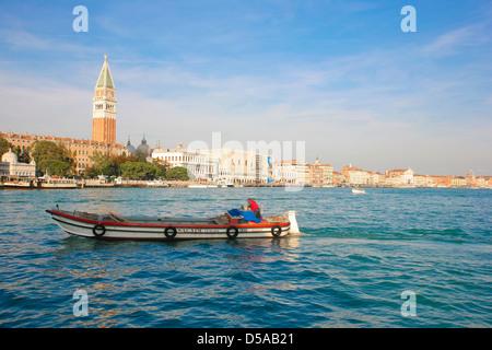 Barco de pesca, pasando por delante de la torre campanario en el gran canal de Venecia, Italia