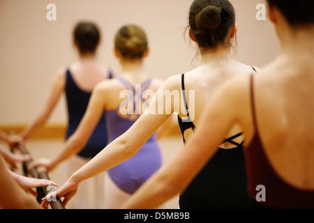 Mujeres adolescentes estudiantes de ballet sosteniendo una barra de ballet en una escuela de ballet en el reino unido