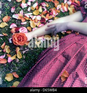 Una niña en un vestido rojo está tumbado en la hierba de entre pétalos, una rosa en su mano