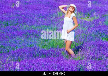 Pretty girl curtido en la lavanda glade, disfrutando de la luz del sol brillante y flores púrpura paisaje, divertirse al aire libre en verano