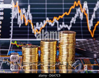 Subida apila monedas, cubos cubo con la palabra GO y calculadora de los gráficos de cotizaciones financieras como fondo. Enfoque selectivo