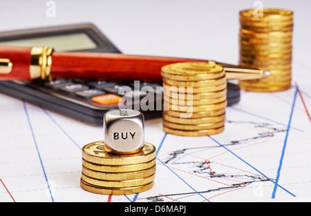 Subida monedas pilas, calculadora, lápiz y cubos cubo con la palabra comprar en cuadro de financiación. Enfoque selectivo