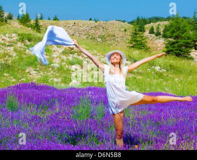 Hermosa joven bailando en el campo de lavanda púrpura, vestida de elegante traje y sombrero blanco, sosteniendo en la mano un chal