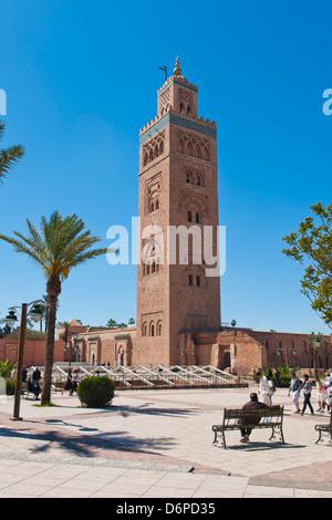 El hombre marroquí sentado en un banco en frente de la Mezquita de Koutoubia, Marrakech, Marruecos, África del Norte, África Foto de stock