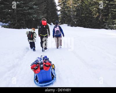 Familia caucásica tirando el trineo a través de la nieve Foto de stock