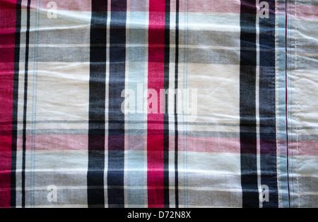 Primer plano de una camiseta material de tela y cuadrado rojo azul negro ornamentos de fondo.