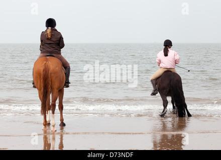Dos mujeres jóvenes sobre caballos a caballo en la playa en el Waters Edge Holkham Beach Norfolk UK