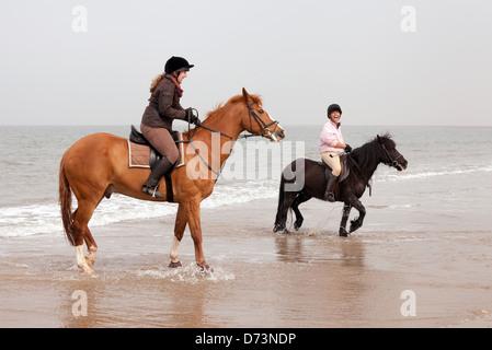 Dos mujeres jóvenes montando a caballo en Holkham Beach, al norte de la costa de Norfolk, East Anglia, en el REINO UNIDO
