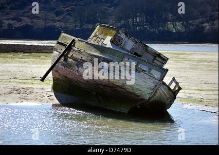 Viejo barco abandonado pudriéndose lentamente en un estuario con marea baja.