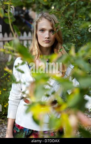 Hermosa teen detrás de árbol en el jardín