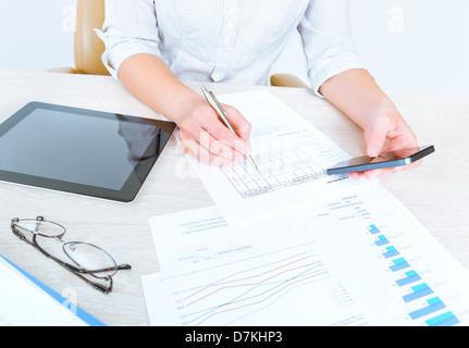Exitosa empresaria sentados frente al escritorio en ropa casual y utilizando los dispositivos modernos para analizar las estadísticas de ventas