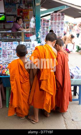 Tres monjes novicios comprando comics en el mercado de la ciudad, Kengtung (Kyaingtong), el Estado de Shan, Birmania Foto de stock