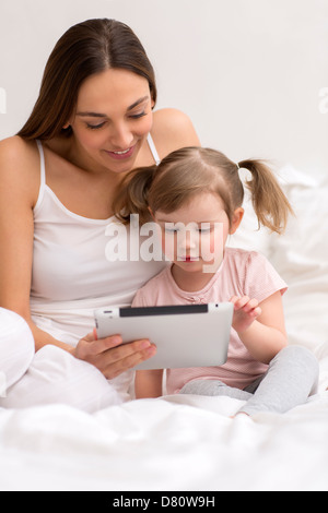Niña jugando tablet con su mamá en el dormitorio blanco