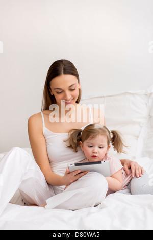 Niña jugando tableta digital con su mamá en el dormitorio blanco