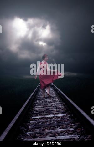 Una niña en un vestido rojo se está ejecutando en las vías del ferrocarril Foto de stock