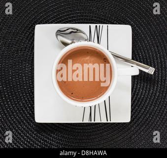 Bebida de chocolate caliente en taza y plato blanco sobre negro tablemat