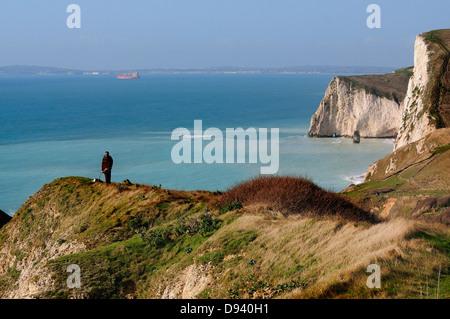 Una vista de la costa de Dorset con un artista en la cima del acantilado