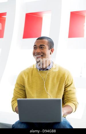 Hombre de raza mixta con ordenador portátil y auriculares