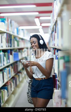Estudiante escuchar el reproductor de mp3 en la biblioteca Foto de stock