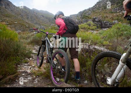 Mujer joven empujando hacia arriba mountain bike camino de montaña. Foto de stock