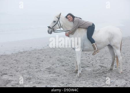 La mujer a caballo en la playa Foto de stock