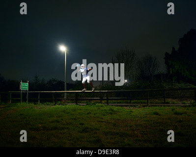 Jugador de fútbol americano tomando distancia de valla