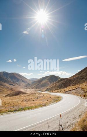 Larga y serpenteante carretera a través de un valle, Otago, Isla del Sur, Nueva Zelanda