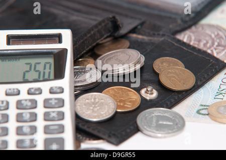 Dinero - zloty polaco, billetes de banco, monedas, calculadora y monedero sobre fondo blanco.