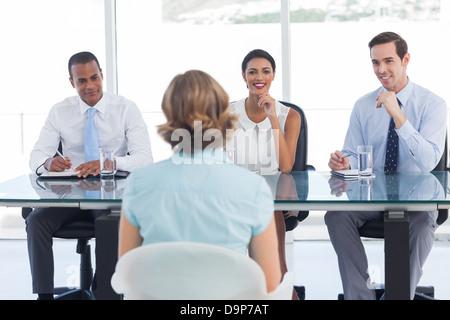 Contratación de consultores sonriendo delante de un solicitante de empleo