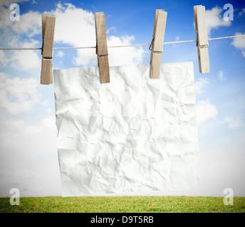 Papel arrugado blanco colgado en una línea de lavandería