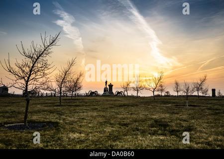 Monumentos, Cannon y árboles en el huerto de durazno en el Parque Militar Nacional de Gettysburg al amanecer.