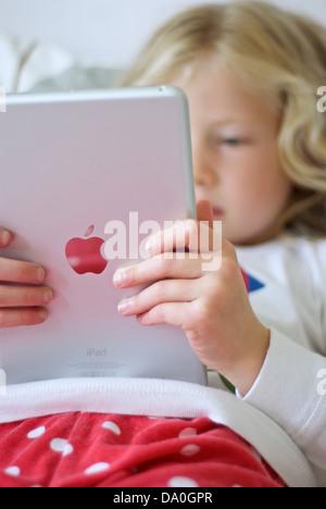 Niña usando un iPad mini Foto de stock