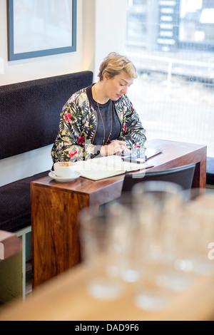 Mujer con digital comprimido en cafe