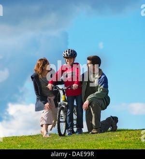 El padre y la madre alentando al hijo a andar en bicicleta Foto de stock