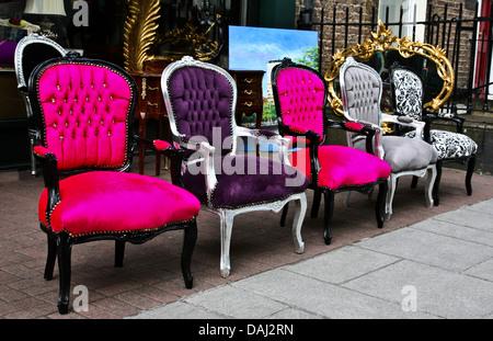 Colorido cierre exterior sillas antiguas Victoriana aparece en una fila delante de una tienda de antigüedades en Dublín, Irlanda, objetos vintage, presidente resumen