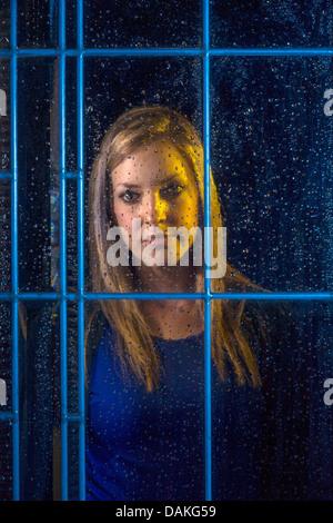 Una adolescente mira una ventana en una noche lluviosa con una grave expresión en Laguna Beach, California. Foto de stock